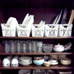 食器棚に皿を入れた籠を置いた画像